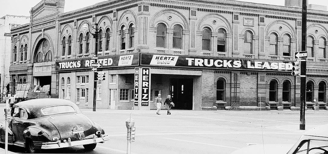 A black and white photo showing the street view of a Hertz location in Denver City, Colorado in 1959.