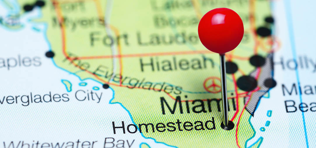 A red pin is stuck in a point, marking Homestead, Florida on a close-up image of a map.