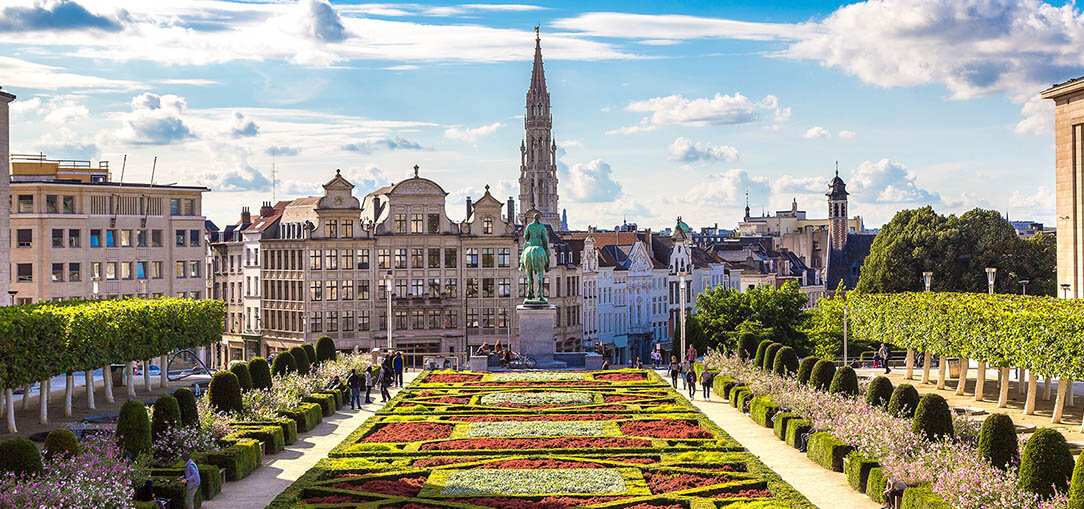 A bright green and red patterned garden sits in the foreground with beautifully groomed bushes and trees on either side, with the buildings making up the skyline of Brussels, Belgium in the background against a bright blue sky with fluffy clouds