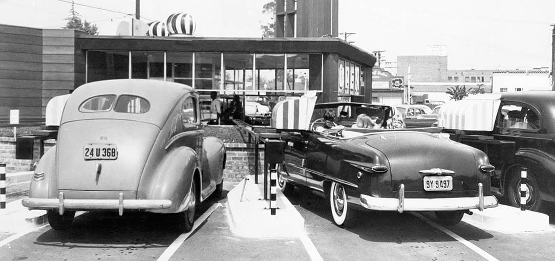 The backs of old vehicles are pictured in a black and white photo