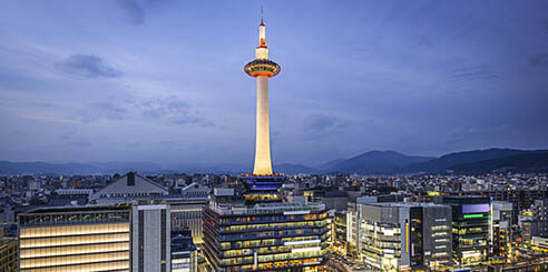 A cityscape view of Kyoto Tower lit up in the evening, standing high above all other buildings in downtown Kyoto, Japan