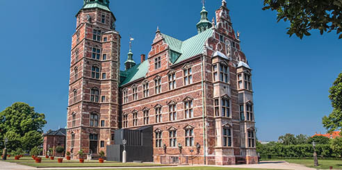 The light pink brick exterior of the Rosenberg Palace in Copenhagen, Denmark, is seen against a bright blue sky and bright green leafy trees