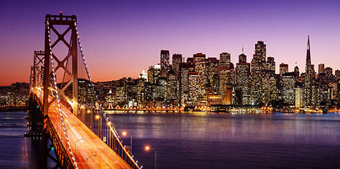 Panoramic view of San Francisco skyline with the buildings illuminated behind Bay Bridge, also lit up, at sunset over the water