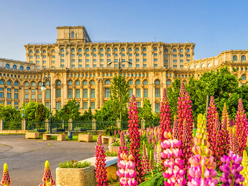 View of the entrance of The Palace of Parliament in Bucharest, Romania with vibrant pink, red, and yellow flowers and green trees in the forefront