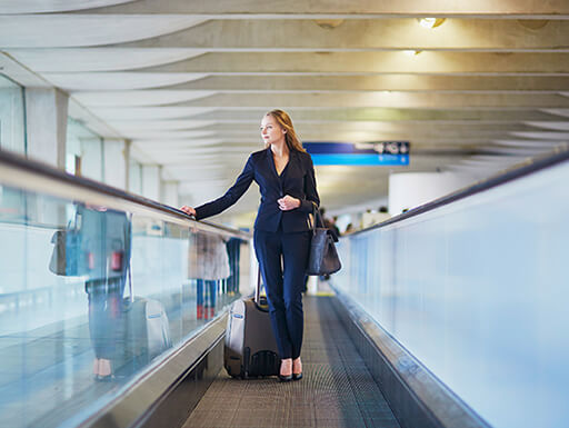 Business woman in suit stands on moving walkway in the airport with a black carry-on bag.