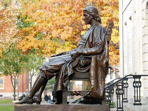 Side profile of the John Harvard statue in Cambridge, taken during the American History Tour, in front of orange and yellow trees on a cool, autumn day.