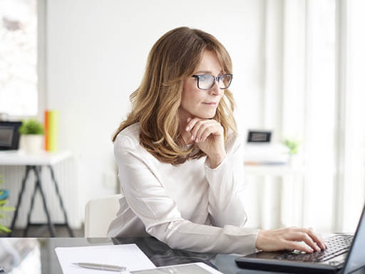 Woman in a white shirt and glasses looks at her laptop in an office.