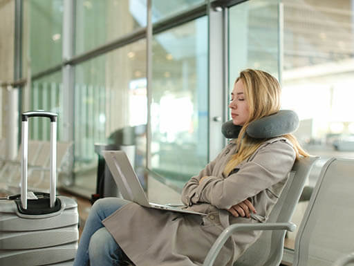 A young woman sits in an airport waiting area with a neck pillow and laptop.