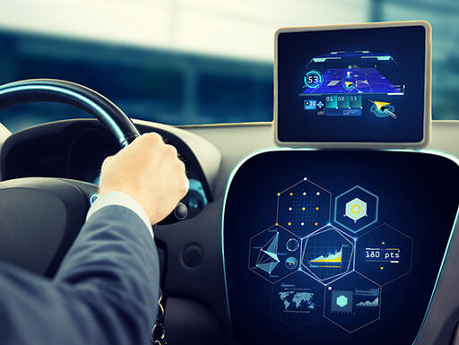 A close view of a person driving a car with an advanced in-dash system and a tablet with various charts