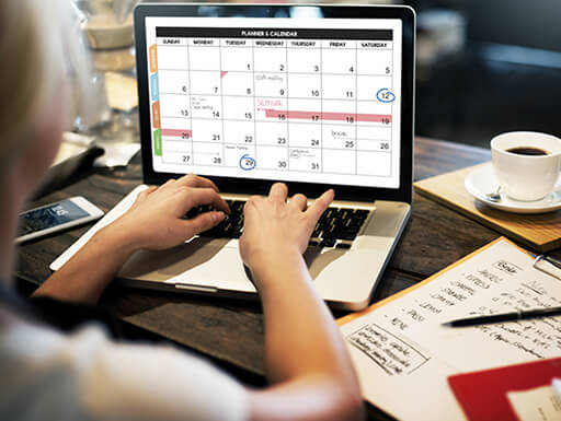A woman reviews calendar events on her laptop