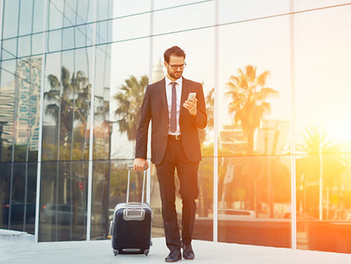 Business man looks at his phone while walking through the airport as the sun sets against a wall of windows reflecting cars and palm trees.