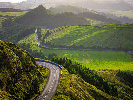 Winding road on side of cliff overlooking lush green mountains