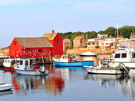 Boats docked at Rockport Massachusetts coastline in front of a large red building on a picturesque summer afternoon.