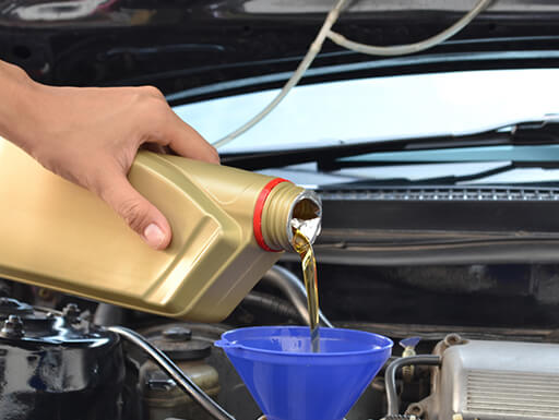 A hand pours oil into a funnel under the hood of a car during an oil change