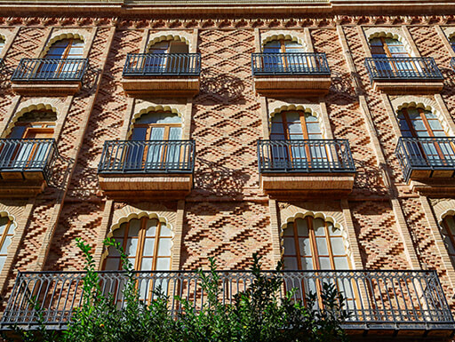 Gorgeous and intricately detailed brick buildings with balconies in Valencia's Ruzafa neighborhood a summer afternoon.