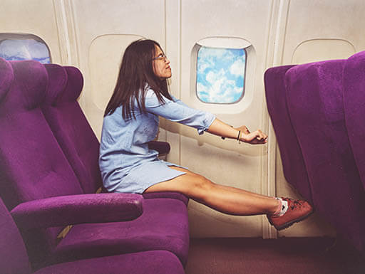 A young woman stretches out her legs while sitting in purple business class airplane seat.
