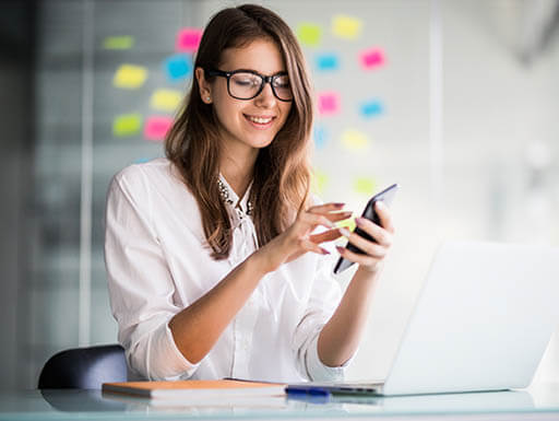 A young woman smiles at her desk while looking at her smartphone.