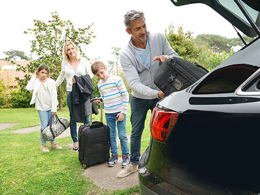 Family of four happily pack their vehicle with luggage as they get ready to leave for a vacation