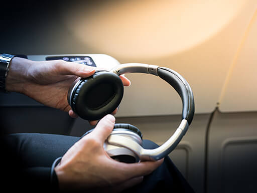 A man holds neutral-colored headphones in his hands on an airplane.