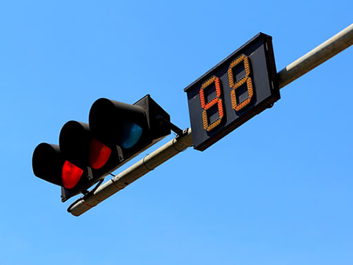 A traffic light sits next to a countdown sign with a bright blue sky in the background