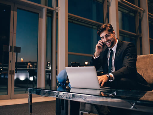 Business man talks on the phone while looking at his laptop on a late evening layover in the airport.