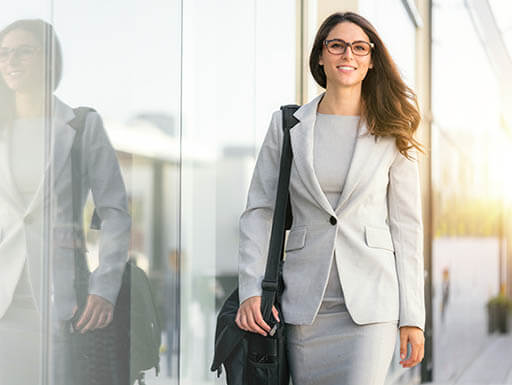 A woman wearing glasses and an off-white business suit walks confidently with a computer bag over her shoulder.