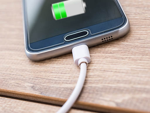 An up-close view of a silver smartphone plugged into a charger.