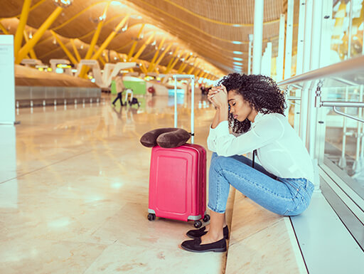 A woman sits with her head in hands at an airport with a pink suitcase at her side.