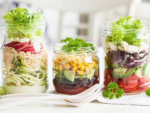 Three different types of healthy salads are lined up on a table in mason jars while meal prepping.