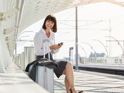 Business woman smiles next to her carry-on luggage while using her smartphone in an airport on a cloudy day.