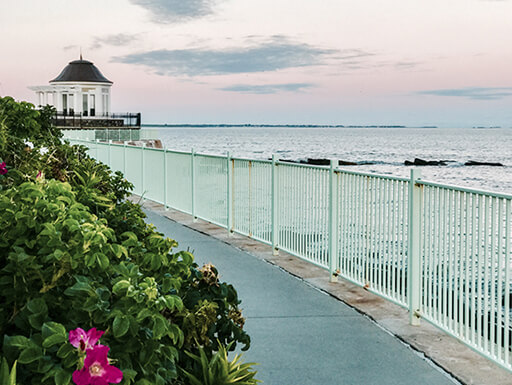 Newport, Rhode Island's cliff walk along the coast, lined with a white railing and leafy greenery with pink flowers shows a white gazebo in the background along the Atlantic coast.