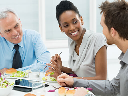 A group of three business people smiling while having a working lunch meeting.