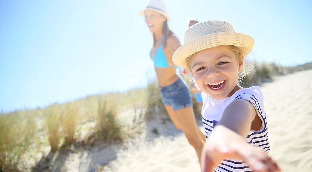 Little girl wearing a hat and striped shirt smiles at the camera with woman in turquoise swimsuit on a sunny beach