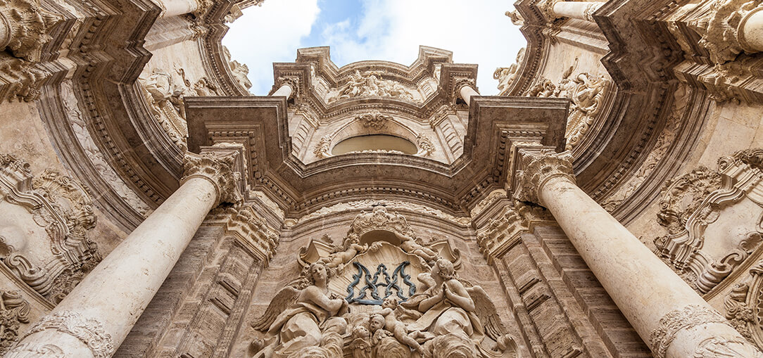 A detailed shot looking upward at carved stones and columns inside of the Valencia Cathedral in Spain on a partly cloudy day.
