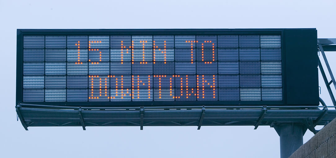An LED sign sits over a highway indicating how many minutes to your destination