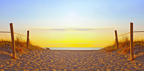 Sunrise on a sandy pathway dotted with footprints to beach