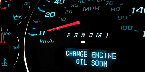 A car dashboard shows a speedometer and below it a warning to change oil soon