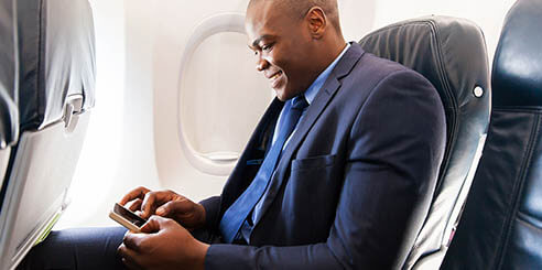 A businessman smiling at his smartphone while on an airplane