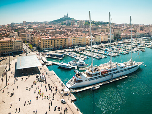 A view of the old port area in Marseille shows rows of fishing boats docked, and a larger yacht, in the water while visitors meander on the port on a sunny day in France.
