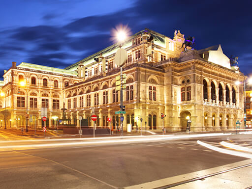 Vienna 's State Opera House brightly illuminated at night with a dark navy sky in the background.