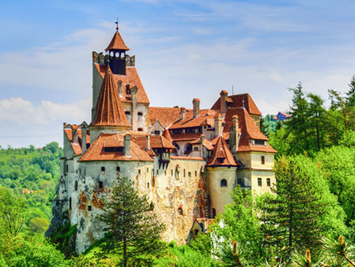 Bran Castle in Romania, also known as Dracula's Castle, is a historic stone castle with a red roof surrounded by lush green trees near Bucharest.