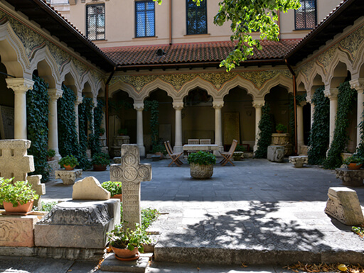 The courtyard of Stavropoleos Monastery in Bucharest's Lipscani neighborhood shows ornate columns and ivy surrounding the courtyard with trees providing shade on a bright spring day.