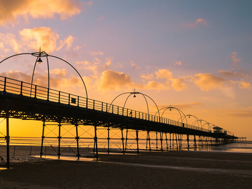 Silhouette of The Pier at Southport at sunset with golden clouds in the sky.