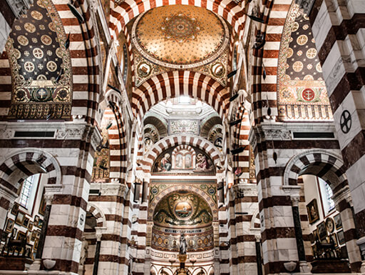 The ornate interior of Notre Dame de la Garde in Marseille, France shows striped columns and walls and beautifully detailed ceilings in the basilica.