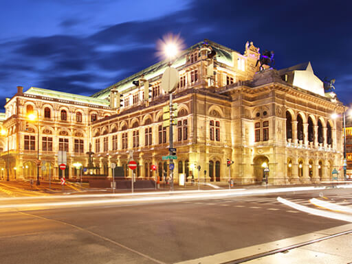 A view of the Vienna State Opera House illuminated at night in the Innere Stadt neighborhood.
