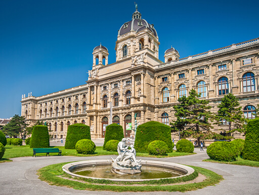 Vienna's Naturhistorisches Museum (Natural History Museum) with a green park and stone sculpture on a bright sunny day.