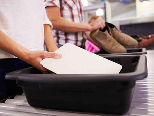 A traveler goes through the TSA security screening process and places their laptop in a bin at a brightly lit airport.