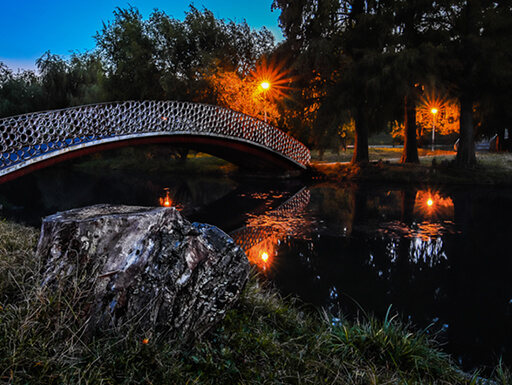 An ornate pedestrian bridge over a stream in Tineretului Park in Bucharest at dusk with light posts glowing in the background.