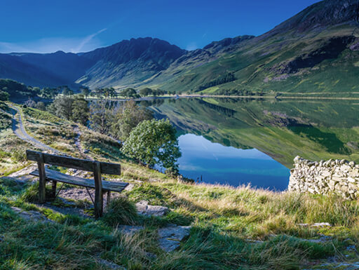 View of Buttermere in Cumbria, England shows water reflecting the nearby green mountains with a bench and stone wall in the foreground on a clear day.