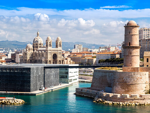 The port area of Marseille including MuCEM, Fort St. Jean and Cathedral de la Major shown on a sunny summer day with white puffy clouds in the distance.